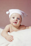 Cute little baby. Cute smiling little baby in white hat Stock Image