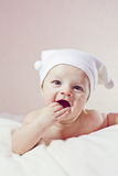 Cute little baby. Cute laughing little baby in white hat lying down on white blanket Stock Image