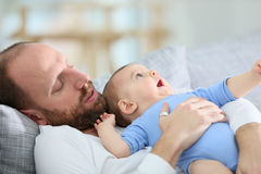 Cute little baby in the arms of his father lying on the sofa. Father with baby boy relaxing in sofa at home royalty free stock images