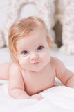 Cute little baby in bedroom. Cute little baby with big blue eyes  lies down on the bed, smile and looks towards Stock Photos