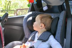 Cute little baby boy in car safety seat looking at the window. Royalty Free Stock Photos