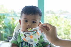 Cute asian baby bored with food. Cute little baby boy eating food stock images