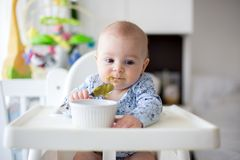 Cute little baby boy, eating mashed vegetables for lunch, mom fe Royalty Free Stock Photo