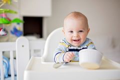 Cute little baby boy, eating mashed vegetables for lunch, mom fe. Eding him, sweet toddler boy, smiling Stock Images