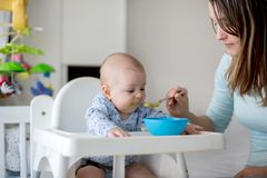 Cute little baby boy, eating mashed vegetables for lunch, mom fe. Eding him, sweet toddler boy, smiling royalty free stock photography