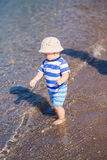 Cute little baby boy exploring the beach Stock Image