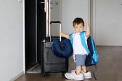 Cute little baby boy in fathers sneakers and with big backpack holding suitcase and waving goodbye staying at open door ready to t Royalty Free Stock Photography