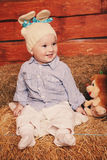 Cute little baby boy in funny bunny hat lying on straw Royalty Free Stock Image