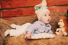 Cute little baby boy in funny bunny hat lying on straw Royalty Free Stock Photos