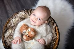 Cute little baby boy with handmade knitted cloths, playing with. Little teddy bear toy, smiling at camera Royalty Free Stock Images