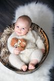 Cute little baby boy with handmade knitted cloths, playing with. Little teddy bear toy, smiling at camera Royalty Free Stock Image