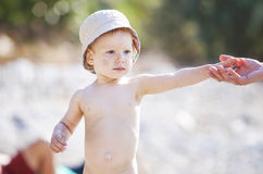 Cute little baby boy holding mom's hand while walking. On beach Stock Image