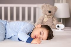 Cute little baby boy in light blue pajamas sleeping peacefully on bed at home with baby monitor camera and soft teddy bear toy at royalty free stock photos