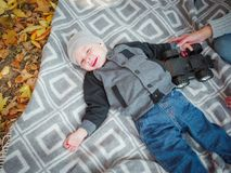 Cute little baby boy lying on a blanket in an autumn park. royalty free stock photography