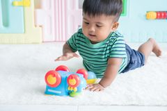little baby boy lying on the floor and play toy car stock photography