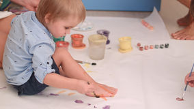 Cute little baby boy painting his feet on a large blank white paper Royalty Free Stock Images