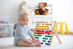 Cute little baby boy, playing with abacus at home. Sunny kids room Stock Image