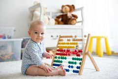 Cute little baby boy, playing with abacus at home. Sunny kids room Royalty Free Stock Photos