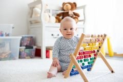 Cute little baby boy, playing with abacus at home. Sunny kids room Royalty Free Stock Images