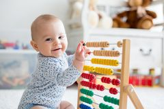 Cute little baby boy, playing with abacus at home. Sunny kids room Stock Images