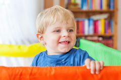 Cute little baby boy playing in colorful playpen, indoors Stock Photos