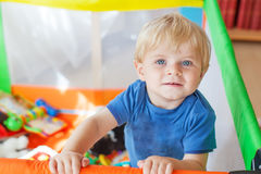 Cute little baby boy playing in colorful playpen, indoors Royalty Free Stock Photography