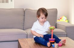 Cute little baby boy playing with colorful wooden pyramid at home. Kids skills development. Eco-friendly materials toy. stock photography