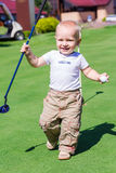 Cute little baby boy playing golf on a field Stock Photos