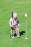 Cute little baby boy playing golf on a field Royalty Free Stock Image
