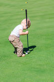Cute little baby boy playing golf on a field Royalty Free Stock Images
