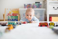 Cute little baby boy, playing with toy cars on the carpet in chi. Cute little baby boy, playing with toy cars on the carpet in sunny kids room Stock Image