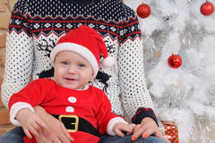 Cute little baby boy in Santa suit sitting on mother's knees on Stock Image