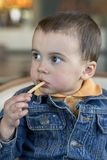 Cute little baby boy sitting at cafe eating tasty french fries. European royalty free stock photography