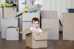 Cute little baby boy sitting inside cardboard box with big boxes full of toys on background Royalty Free Stock Photos