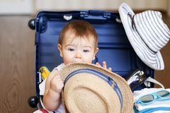Cute little baby boy inside packed suitcase with straw hat in his hands. Cute little baby boy sitting inside packed suitcase with straw hat in his hands and Stock Images