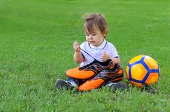 Cute little baby boy sitting with orage soccer ball on green grass holding football boots in his hands. And looking at laces. Future of football concept royalty free stock photo