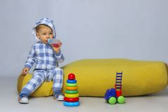 Cute Little Baby Boy Sitting On a Yellow Bean Bag Chair and Playing Toys. Shot of a little baby boy playing with some toys and drinking from a sippy cup royalty free stock photography