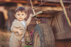 Cute little baby boy standing near metal fence in autumn yard Royalty Free Stock Images