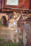Cute little baby boy standing near metal fence in autumn yard Stock Photo