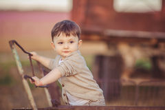 Cute little baby boy standing near metal fence in autumn yard Royalty Free Stock Photography