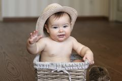 Cute little baby boy in straw hat sitting in the box Royalty Free Stock Photo