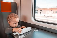 Cute little baby boy traveling by railway. Cute little kid boy in a white t-shirt looking at the city out of the train window. Child traveling by railway. young royalty free stock photography