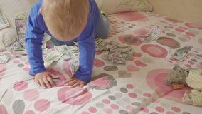 Cute little baby boy under a dollar rain in bed. Concept of heritage. Cute little baby boy under a dollar rain in bed. Concept of heritage hd stock footage