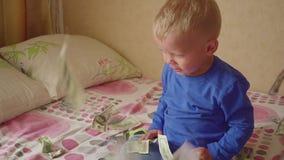 Cute little baby boy under a dollar rain in bed. Concept of heritage. Cute little baby boy under a dollar rain in bed. Concept of heritage hd stock video footage