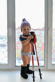 Cute little baby boy weared in winter clothes playing with trekking sticks standing near the window, high city buildings at backgr Royalty Free Stock Photo