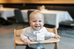 Cute little baby boy in white polo t-shirt sitting in wooden baby chair and laughing at cafe indoors. Portrait of. Adorable blond kid having fun at restaurant royalty free stock photo