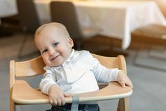 Cute little baby boy in white polo t-shirt sitting in wooden baby chair and laughing at cafe indoors. Portrait of. Adorable blond kid having fun at restaurant stock photos