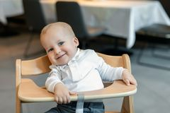 Cute little baby boy in white polo t-shirt sitting in wooden baby chair and laughing at cafe indoors. Portrait of. Adorable blond kid having fun at restaurant stock photo