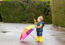Cute little baby boy in yellow rubber boots with colorful rainbow umbrella staying on wet road after rain pointing with his finger royalty free stock images