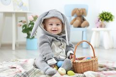 Cute little baby in bunny costume playing with Easter eggs. At home stock photos